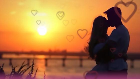 Силуэты целующихся парня и девушки на фоне восходящего солнца и контурных сердечек