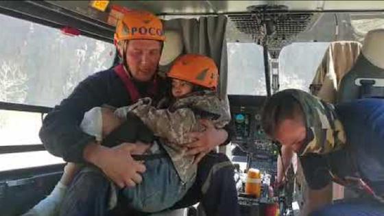 Спасатель держит спасенного ребенка