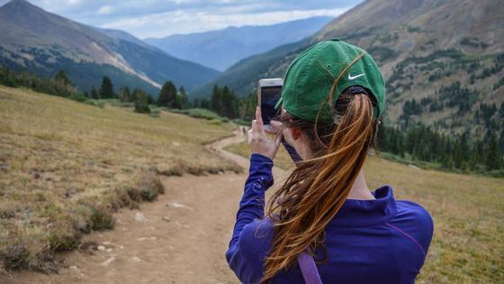 Девушка направляет телефон в сторону степи