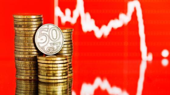 Монеты тенге лежат стопкой на фоне графика