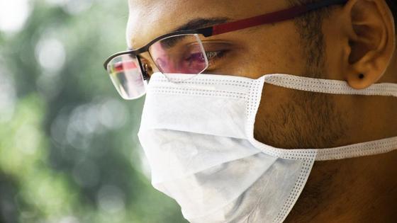 Мужчина в маске смотрит в сторону