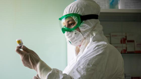 Медик набирает лекарство шприцем из ампулы
