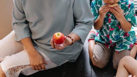 Женщина сидит с детьми