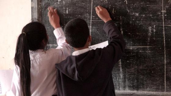 Дети чертят мелом на школьной доске