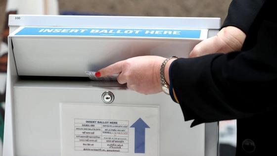 Женщина опускает бюллетень в ящик для голосования