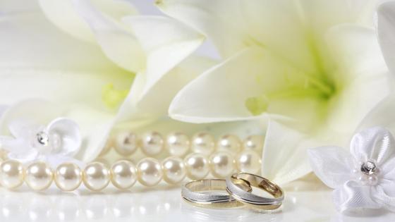 Обручальные кольца возле жемчуга и лилий