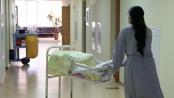 Медик везет каталку в роддоме