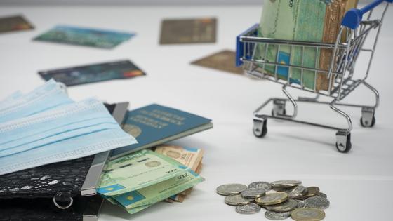 Пачка тенге лежит в миниатюрной тележке между дукоментами, банковскими картами и масками