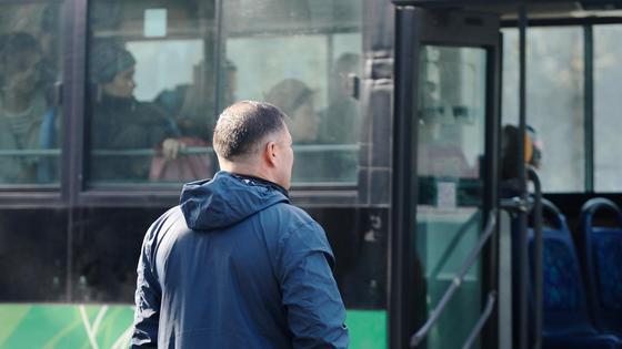 Мужчина идет в сторону автобуса