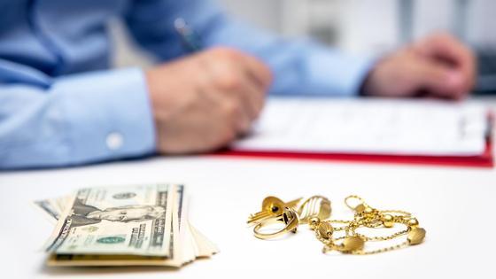 Работник ломбарда выдает микрокредит под залог золота