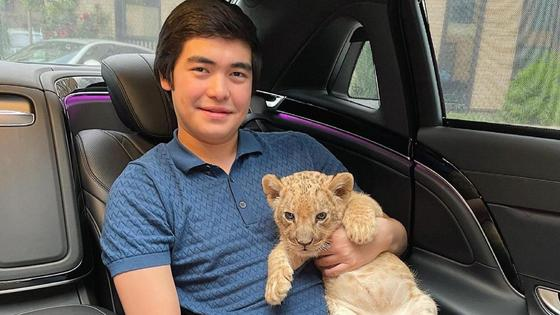 Алихан Байзаков держит львенка на руках