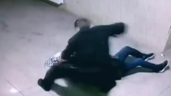 Мужчина наносит удар лежащей на полу женщине