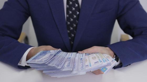 Мужчина в строгом костюме и галстуке держит в руках большую сумму денег
