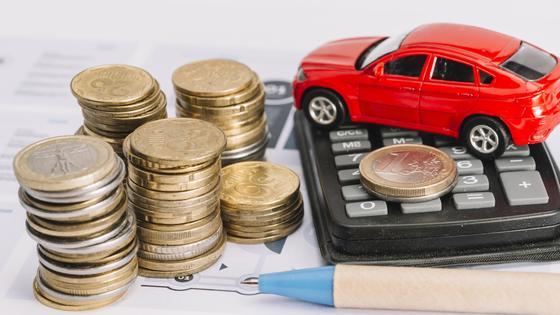 Игрушечная машинка стоит на калькуляторе рядом с монетами и ручкой