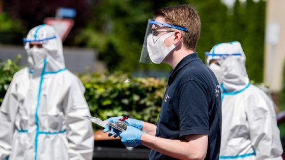 Мужчина в защитной маске и с защитным экраном стоит рядом с медиками в костюмах