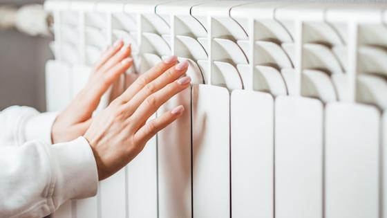 Женщина греет руки у батареи
