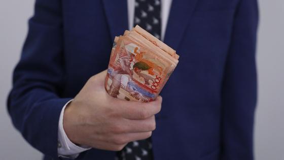 Мужчина в костюме держит пачку денег