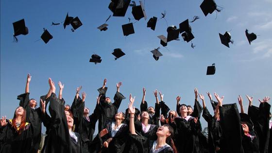 Студенты-выпускники в мантиях подбрасывают в небо головные уборы