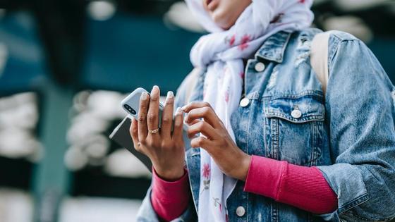 Девушка в платке держит в руках телефон