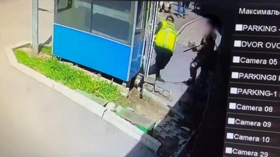 Мужчина в камуфляжной форме стреляет в охранника ЖК