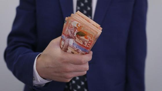 Человек в костюме держит пачку денег в руках