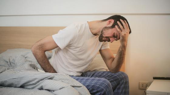 Мужчина сидит на кровати и держит голову