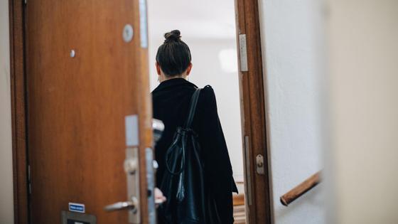 Женщина в черной одежде заходит в помещение