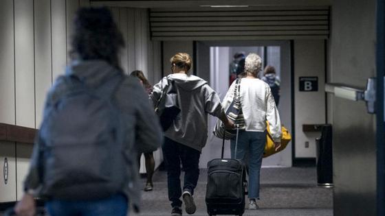Пассажиры с сумками идут по коридору