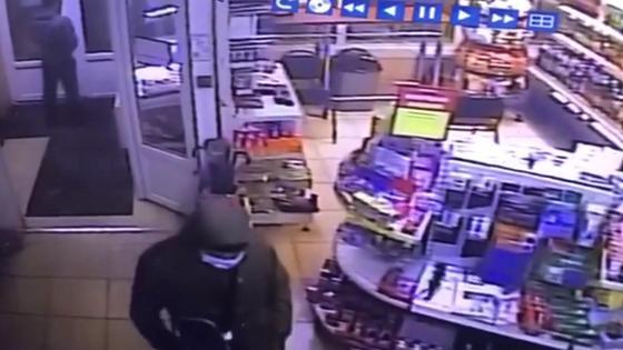 Мужчина в маске и капюшоне стоит посреди магазина