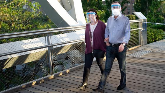 Мужчина и женщина идут по мосту в щитах для лица