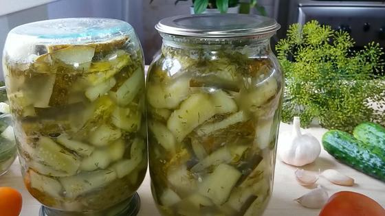 В литровых банках салат из огурцов и на столе чеснок, свежие огурцы, укроп