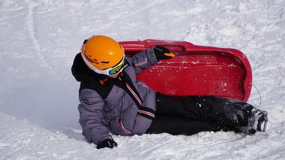 Женщина скатилась на санях с ледяной горки