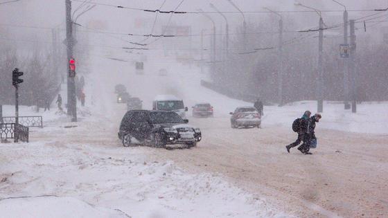 Школьники переходят дорогу во время снегопада