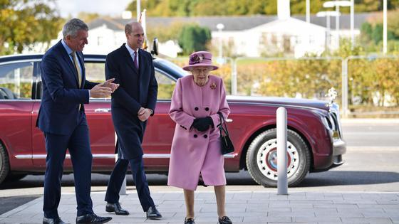 Королева, ее внук и еще один мужчина идут по улице