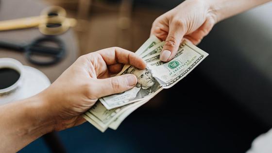 Двое людей передают доллары из рук в руки