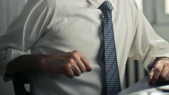 Мужчина в рубашке и галстуке сидит за столом