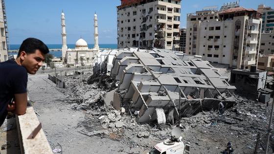 Человек смотри на разрушенное здание в секторе Газа