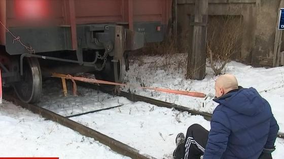 Ер адам 26 тонналық вагонды тісімен сүйреді
