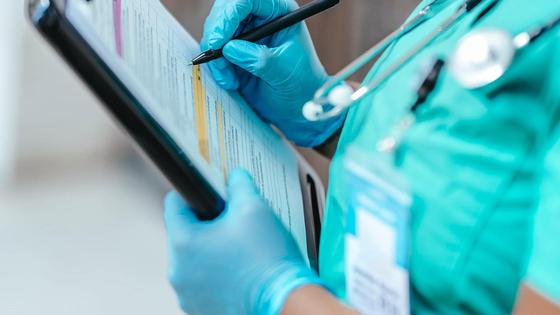 Медик держит в руках папку