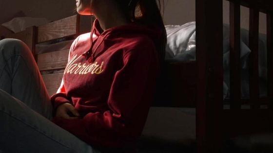 Девушка сидит на полу и смотрит в окно