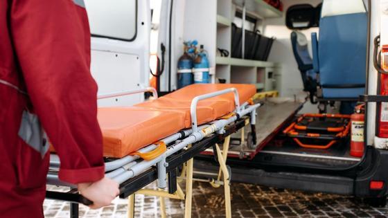 Работник скорой помощи заносит койку в карету
