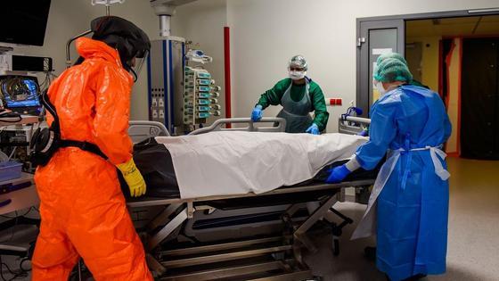 Медики в защитных костюмах перевозят каталку, накрытую простыней