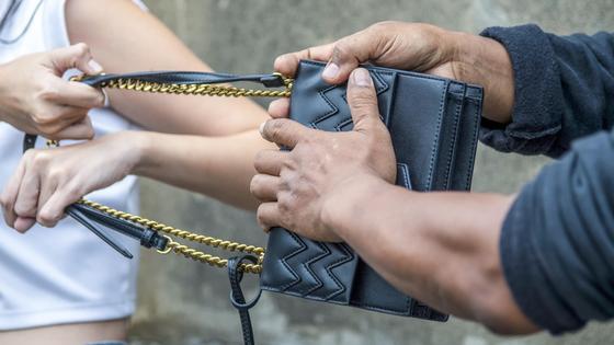 Мужчина вырывает сумочку из рук у женщины