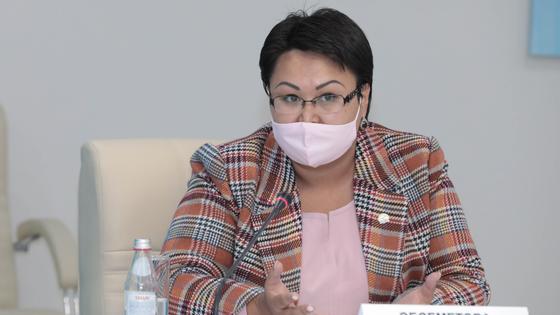 Женщина в костюме сидит за столом