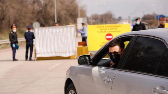 Водитель в черной маске выглядывает из автомобиля