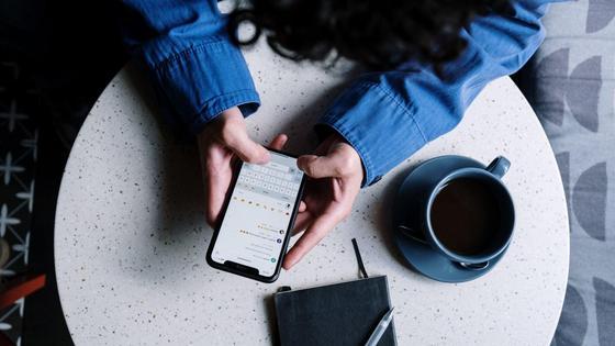 Девушка сидит за столом с телефоном в руках