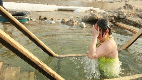 Женщина купается в реке на Крещение