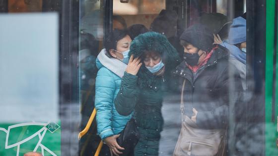 Люди стоят в автобусе в масках и в верхней одежде