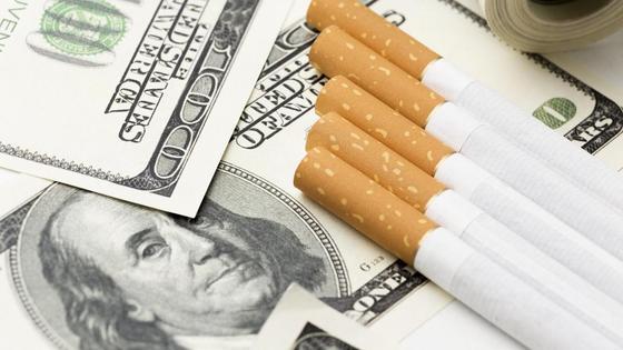 Сигареты лежат на долларовой купюре