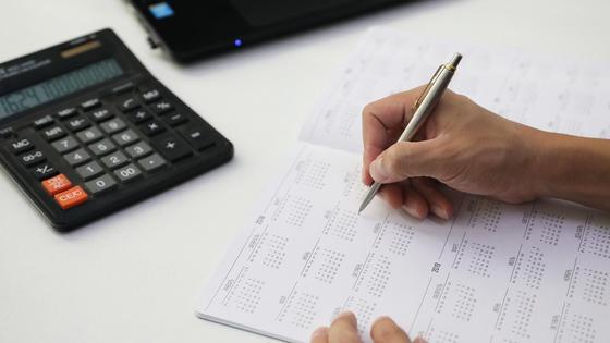 Человек пишет на листе за столом
